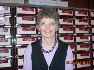 Town Clerk Donna La Plante in front of the land records volumes
