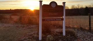 New Hartford sign with sunrise behind it